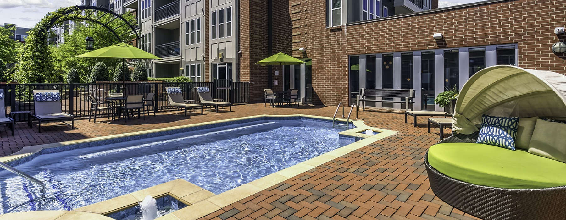 Pool with shaded lounge seating by tall brick apartment building